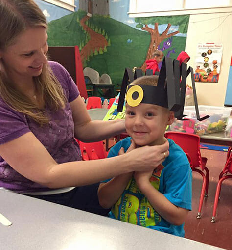 Teacher Debbie Helping Student Adjust His Spooky Spider Hat